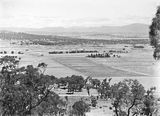 Picture relating to Canberra - titled 'View from Mt Ainslie showing Anzac Parade, St John's Church, Old Parliament House, Hotel Canberra, Commonwealth Bridge and Scotts Crossing.'