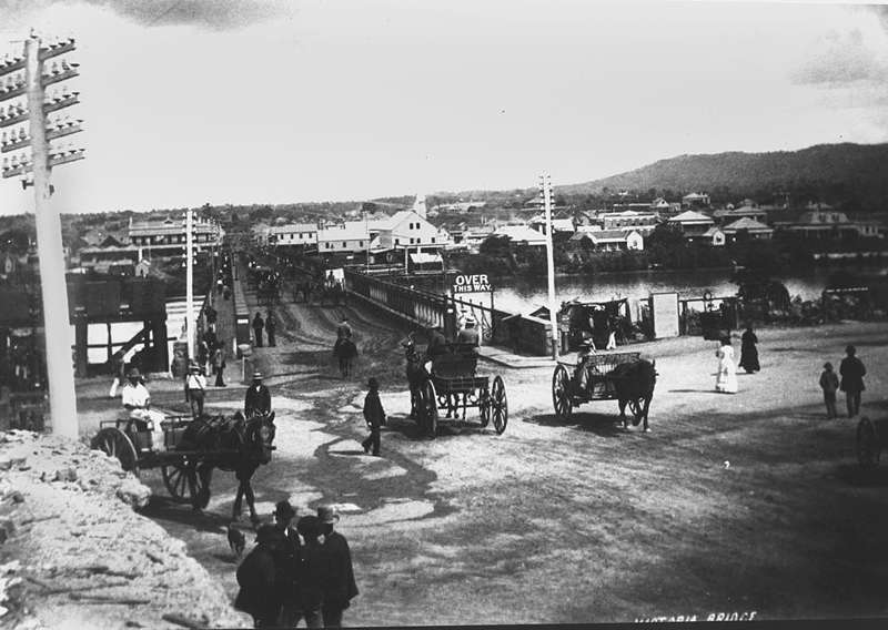 Picture of / about 'Brisbane' Queensland - Horsedrawn carriages and pedestrians at the northern approach to the first permanent Victoria Bridge, Brisbane, ca. 1885