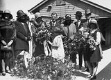 Picture relating to Canberra - titled 'Mrs Scullin being presented with flower bouquets by children on Canberra railway station'