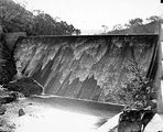 Picture relating to Cotter Dam - titled 'Cotter Dam wall with water flowing over the spillway into the stilling pond'