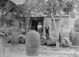Picture relating to Coominya - titled 'Henry Banff and Mr. Serisier standing next to barrels at Clinton Winery, Coominya, ca. 1912'
