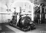 Picture relating to Kingston - titled 'Robey Hall 150 kW twin cylinder, double expansion steam engine coupled to a 150 kW alternator at Kingston Power Station. Note: white steam lines in background delivering steam from the boilers.'