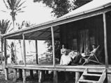 Picture relating to Queensland - titled 'Man and woman relaxing on the verandah of their farmhouse, 1911'