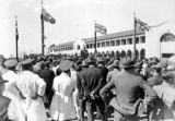 Picture relating to Bruce - titled 'Formal opening of Civic Centre by Prime Minister S. M. Bruce. Part of the crowd, Men in white coats are bus drivers.'