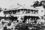 Picture relating to Stanthorpe - titled 'Caves Boarding House with guests lining the balcony and relaxing in the grounds, Stanthorpe, ca. 1917'