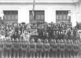 Picture relating to Parliament House - titled 'Bert Hinkler being welcomed by Prime Minister S. M. Bruce in front of Old Parliament House with Royal Military College Cadets and spectators.'