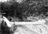 Picture relating to Cotter Dam - titled 'Cotter Dam below the wall;stilling pond is dry. Footbridge across Cotter River on the left.'