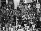 Picture relating to Brisbane - titled 'Crowd on Queen Street, Brisbane, watches the Seventh Division troops pass by the General Post Office'
