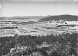 Picture relating to Ainslie - titled 'Braddon, Reid and Civic Centre from Mt Ainslie. Ainslie Hotel, Limestone Avenue in foreground. Black Mountain in background.'