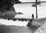 Picture relating to Cotter Dam - titled 'Cotter Dam Wall and stilling pond. Fisherman fly casting into the pond.'