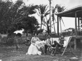 Picture relating to Queensland - titled 'Two men and a woman taking tea on the lawn, 1911'