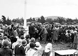 Picture relating to Ainslie - titled 'Mrs Bruce receiving a bouquet with a crowd of children at opening of Ainslie School'