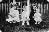 Picture relating to Queensland - titled 'Three Bauer children sitting on the grass, the girls both holding their celluloid dolls, ca. 1920s'