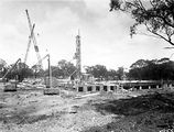 Picture relating to Acton - titled 'Australian Institute of Anatomy foundations with cranes and cement elevator. McCoy Circle, Acton.'
