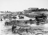 Picture relating to Kingston - titled 'Cletrac Tractor towing wagons carrying river gravel in Molonglo River near the Kingston Power Station, Note Footbridge across the Power Station weir to Duntroon.'