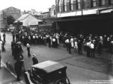 Picture relating to Brisbane - titled 'Crowd gathered for free food outside the McWhirters' building, Fortitude Valley, Brisbane, on Christmas Day 1933'