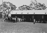 Picture relating to Canberra - titled 'School building with children and crowd at the opening of Mount Russell School, Canberra.'
