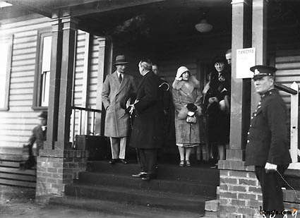 "Picture of / about 'Bruce' the Australian Capital Territory - Royal Visit, May 1927 - Duke and Duchess of York with Prime Minister Rt Hon S M Bruce at Canberra Railway Station Notice on the pillar reads ""Canberra Anglican Cathederal Site. Sunday May 8th Open Air Service""."