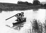 Picture relating to Molonglo River - titled 'Three boys in a home made canoe on the Molonglo River. Note the palings for paddles.'